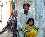 A family bicycles on a street in Lahore, Pakistan.