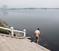 A naked man walks into a river to bathe in Shanxi Province.