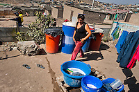 A Peruvian woman washes clothes in buckets outside a wooden house on the dusty hillside of Pachacútec, a desert suburb of Lima, Peru, 20 January 2015. Although Latin America (as a whole) is blessed with an abundance of fresh water, having 20% of global water resources in the the Amazon Basin and the highest annual rainfall of any region in the world, an estimated 50-70 million Latin Americans (one-tenth of the continent's population) lack access to safe water and 100 million people have no access to any safe sanitation. Complicated geographical conditions (mainly on the Pacific coast), unregulated industrialization (causing environmental pollution) and massive urban poverty, combined with deep social inequality, have caused a severe water supply shortage in many Latin American regions.