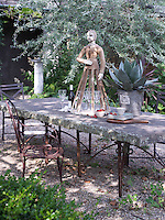Side chairs by Brown Jordan surround a handmade, bluestone-top table in the outdoor dining area. An old dress maker's doll has been appropriated as a glass holder and centre-piece