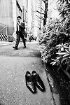 A businessman walks past a pair of well-polished shoes that have apparently been discarded on the sidewalk in Tokyo, Japan.