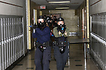 Women police officers in training holding a paint ball simulated gun clearing a school shooting scenario