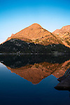 The reflections of mountain peaks in Dewey Lake at sunset. In the Beartooth Wilderness in Montana.