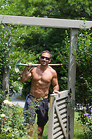 man walking into a yard while carrying a shovel over his shoulder