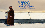 A woman walks alongside a tent in the Zaatari Refugee Camp, located near Mafraq, Jordan. Opened in July, 2012, the camp holds upwards of 50,000 refugees from the civil war inside Syria, but its numbers are growing. International Orthodox Christian Charities and other members of the ACT Alliance are active in the camp providing essential items and services.
