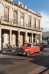 Havana, Cuba; a red classic 1952 Chevy driving down the Paseo de Marti in late afternoon sunlight
