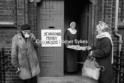 Hoxton, London. 1978<br /> An elderly nun hands out free cups of tea to the needy from St Saviour's Priory annex.