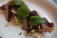 Roasted Leeks with Duck Prosciutoo, Mache, Pignoli, Grilled Red Onion Vinaigrette at Rotisserie Georgette in New York, NY on July 08, 2014. The restaurant has an open kitchen framed in beautiful blue-an-white Portuguese tile.