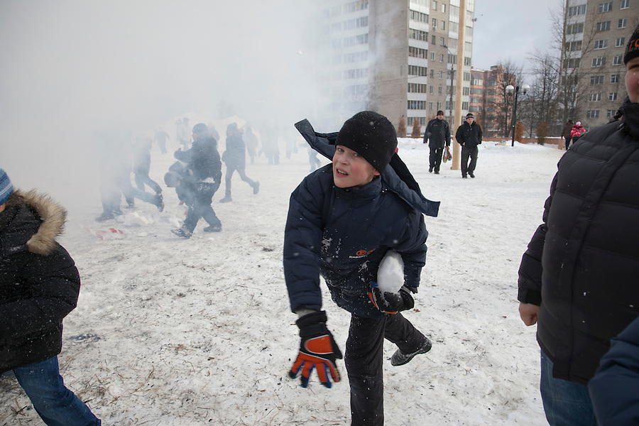 Istra, Russia, 06/03/2011..Children throw snowballs at a burning doll of Lady Maslenitsa as people celebrate Maslenitsa, also known as Butter Week or Pancake Week. Maslenitsa marks the beginning of the Russian Orthodox period of Lent, but is a traditional Russian Holiday marking the end of winter, and has its origins in pagan times.