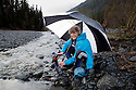WA11252-00...WASHINGTON - Hiker purifying drinking water on a rainy day along the Hoh River in Olympic National Park.  (MR #S1)
