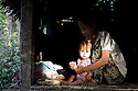 A mother tenderly cleans her child at their home in Mrauk U, Myanmar.  She is applying tanaka, a creme made from wood that is used to protect the skin from the sun.