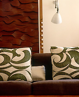 In the living room linen cushions in a 1950's green-and-white Scandanavian design line a sofa situated in front of a wooden relief panel by Brian Willshire
