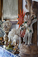 A collection of coral and terracotta lines the mantelpiece in the living room