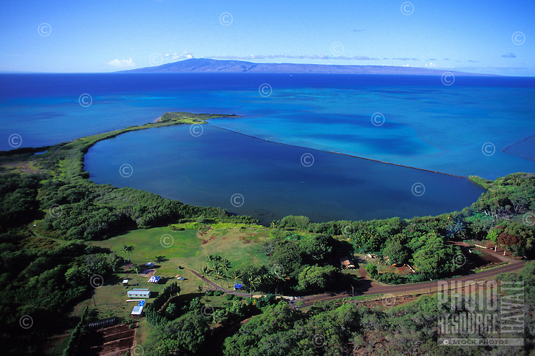 Aerial view of the restored Keawanui Fishpond on the southeastern coast of Molokai, with the island of Lanai in the background