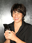 Hispanic woman (20-30) laughs while texting on a mobile phone.