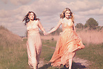 Two happy young women running and wearing pastel colored long dresses