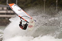 A windsurfer gets some air at Lyall Bay, Wellington, New Zealand