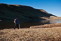 Female hiker hiking along Llyn Y Fan Fawr in Black Mountian, Brecon Beacons national park, Wales