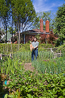 Toronto urban gardener Steven Biggs holds a large onion rope while standing in his kitchen garden.