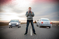 Teenage Boy Standing Middle of the Road and Taking Photos Between Cars