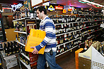 HARWINTON, CT 01/01/09- 010209BZ02- Sales associate Justin Barrante brings cases of champagne and sparkling wine back to the stock room at Tony's Package Store on Rte. 4 in Harwinton Friday night.  He was putting away bottles that did not sell during the New Year's Eve rush.<br /> Jamison C. Bazinet Republican-American