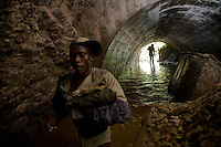 Miners enter the abandoned Makala mine shaft close to Mongbwalu in north eastern D.R.Congo to look for gold-bearing ore deep undrground.They are forced to walk upto 3 KM waist deep in water down disused shafts left behind by mining companies who fled during the countries civil war. Each miner will carry asack of rocks back to the surface which are then broken down in the search for flecks of gold. The mine was first opened in 1948 during Belgium's colonial reign.