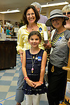 """Huntington, New York, U.S. - August 6, 2014 - A young girl, her mother and another woman are wearing buttons saying """"I'm ready for Hillary"""" as the three wait on line inside the Book Revue at the book signing for the H. Clinton new memoir, Hard Choices, in Huntington."""