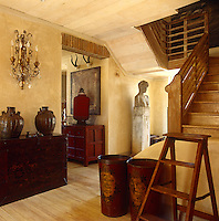 The entrance hall contains an interesting and varied collection of objects including a classical bust and antique trunk used as a hall table