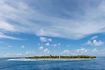 Rangiroa Atoll, Tuamotu Archipelago, French Polynesia; view of Tiputa Village on the western shoreline of Tiputa Pass in early morning sunlight, viewed from within the pass