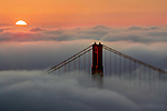 A rising sun over a blanket of fog the engulfs the bay and the Golden Gate Bridge.