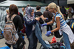 A volunteer found a pair of maternity pants for an expecting refugee mother. Piles of clothes and shoes were donated by Hungarians at a makeshift refugee camp, at the Budapest Keleti railway station.<br /> <br /> Hundreds of refugees from mostly Syria and Afghanistan gather at the Budapest Keleti railway station waiting for trains to leave for destinations such as Austria, Germany and Sweden, in Budapest, Hungary, on Tuesday, Sept. 8, 2015. Hungary's Prime Minister Viktor Orban created an anti-refugee campaign to generate hate against those fleeing war in their home countries. The country is currently 50% xenophobic and the government has become increasingly authoritarian.