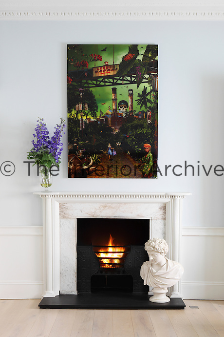 A modern artwork and a classical fireplace make an interesting contrast of styles.