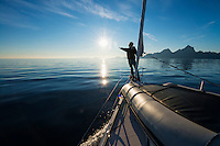 Person reaches for the sun from front of sailboat off the coast of Austvågøy, Lofoten Islands, Norway