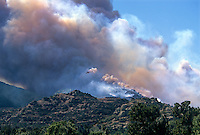 870000378 a los angeles county fire fighting helicopter flies above a burning hillside in the path of the topanga fire in the hills above the san fernando valley in southern california