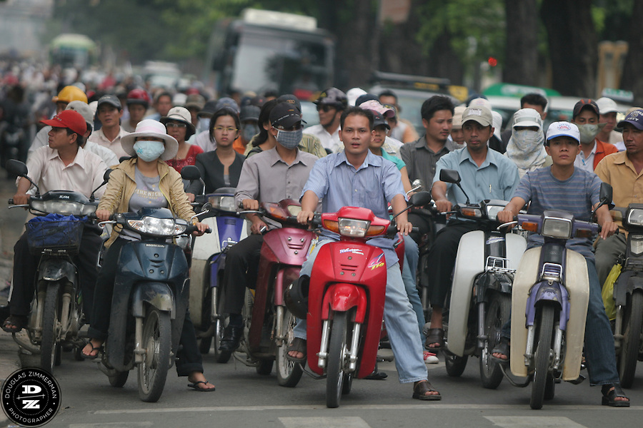 Motorbikes wait at a red traffic light at an intersection in Ho Chi Minh City, Vietnam.  Photograph by Douglas ZImmerman