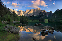 The Mount Mangart reflected in the still waters of the upper lake of Fusine Valromana in Friuli Venezia Giulia, Italy. Probably one of the best natural places in the Giulian Alps, this glacial lake and the surrounding conifer forest are just a gold mine of photo opportunity.