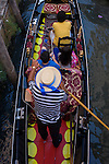 Aerial view of a gondolier and tourists in a narrow canal in Venice, Italy. Current prices (2015) is 80 Euros for a 40-minute journey (earning them approx 130,000 Euros a year) along the waterways of this old city but rarely do gondoliers wear their straw hat.