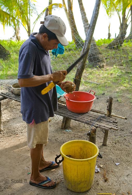 Kuna man prepares a fresh coconut on Isla Pelikano, San Blas Islands, Kuna Yala, Panama