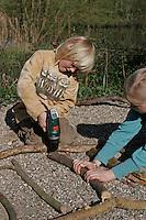 Kinder basteln Klangspiel aus Ästen, Junge bohrt mit Akkubohrer ein Loch in Ast
