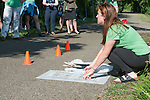 Megan Buskirk, environmental strategies coordinator for Athens City-County Health Department, demonstrates to volunteers how they will be painting mile markers on the HockHocking Adena Bikeway. ©Ohio University / Photo by Kaitlin Owens