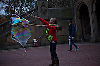 A girl makes soap bubbles Central Park during late autumn in New York . November 11, 2013, Photo by Kena Betancur/VIEWpress.