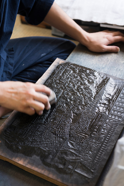 Printer Yoshio Kyoso applying ink to woodblock used to print a modern woodblock print from a design by Akira Yamaguchi. Adachi Foundation for the Preservation of Woodcut Printing, Tokyo, Japan, July 15, 2014. The Foundation works to preserve the original techniques of Japanese woodblock printing. As well as recreating classic ukiyo-e from the Edo period, they train and employ young artisans, and also educate about the art form.