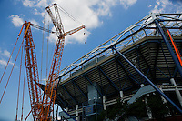 Cranes are seen operated to install the last piece of steel for the roof structure in the Arthur Ashe Stadium at the USTA Billie Jean King National Tennis Center in New York.  06/10/2015. Eduardo MunozAlvarez/VIEWpress