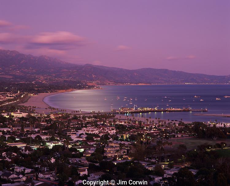 Santa Barbara at sunset with city lights along the Pacific Ocean beach with Stearns Wharf and Santa Ynez Mountain Range in background, Santa Barbara, California USA