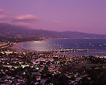Santa Barbara at sunset with city lights along the Pacific Ocean beach with Stearns Wharf and Santa Ynez Mountain Range in background, Santa Barbara, California USA