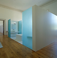 The main bathroom is a room within a room and is built of white marble enclosed with panels of opaque blue glass