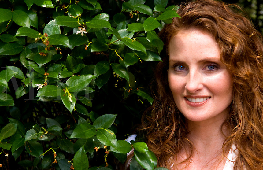 Beautiful red haired Irish woman with blue eyes from Ireland portrait with plants showing beautiful eyes and face