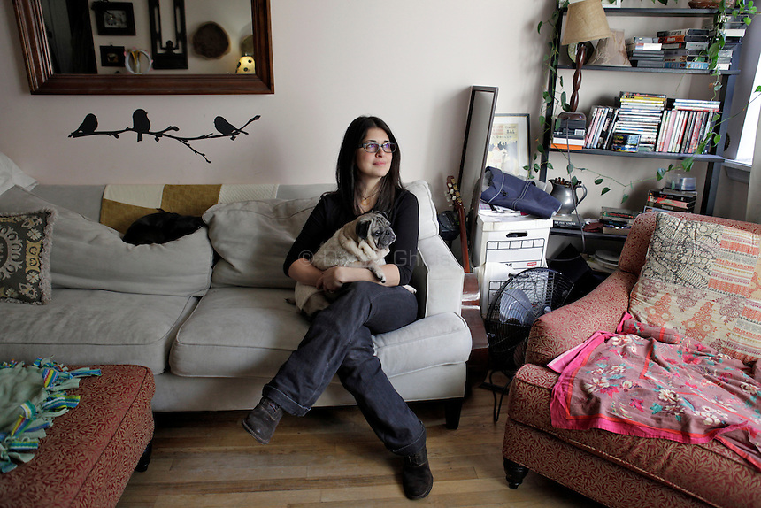 Andréa Peters, 36, an interior designer who also runs the non-profit Curly Tails Pug Rescue, poses for a portrait at her apartment in the East Village with her pugs Chloe Danae, white, and Oliver Grant, black. Chloe suffered from severe allergies until she was put on a raw diet and introduced to a novel protein from elk meat. ..Danny Ghitis for The New York Times