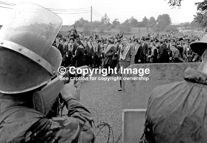 Army &amp; police were in strength on the outskirts of Dungiven, Co Londonderry, to enforce a government ban on an Orange parade through the predominently Nationalist town on 13th June 1971. The parade is halted by soldiers in riot gear. 197106130220f<br />