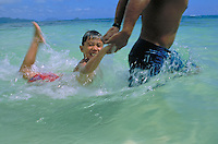 A young local boy plays in the beautiful clear blue ocean with his dad.